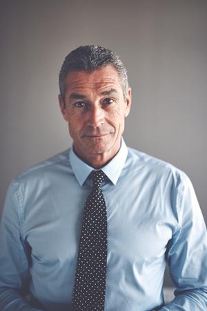 Portret van een knappe volwassen zakenman draagt een shirt en stropdas staan vol vertrouwen alleen in een kantoor Stockfoto