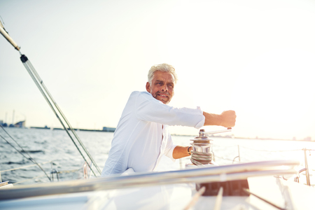 Smiling mature man standing on the deck of a boat winding a winch while out for sailing alone on a sunny afternoon Stok Fotoğraf