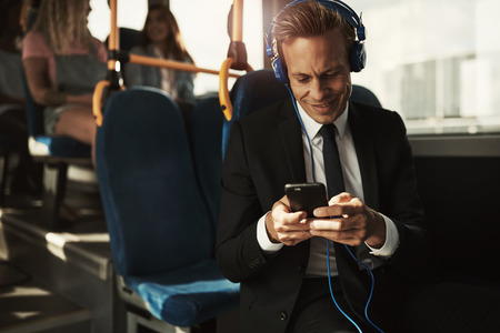 Smiling young businessman wearing a suit sitting on a bus during his morning commute listening to music on headphones and using a cellphone