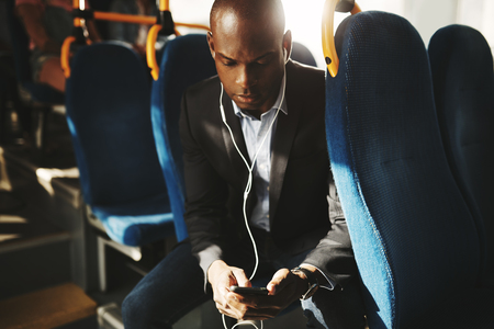Young African businessman wearing a suit sitting on a bus during his morning commute listening to music on a smartphone and headphones