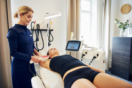 Young female beautician performing an electrolysis hair removal procedure on the underarm of a woman lying on a table in a beauty clinic Stock Photo
