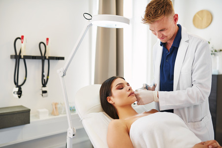 aging face: Young male doctor focused on performing a botox injection to the cheek of a woman lying on a table in a beauty clinic Stock Photo