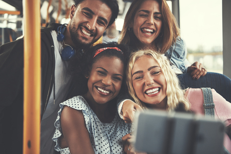 Diverse group of smiling young friends taking selfies while riding together on a bus Archivio Fotografico