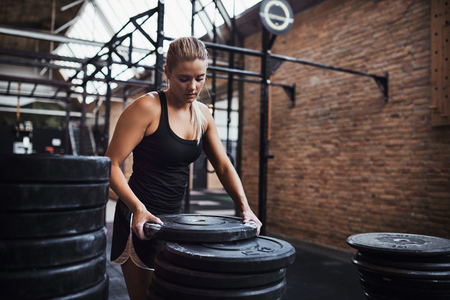 Fit young blonde woman in sportswear standing alone in a gym selecting weights for a workout session Фото со стока