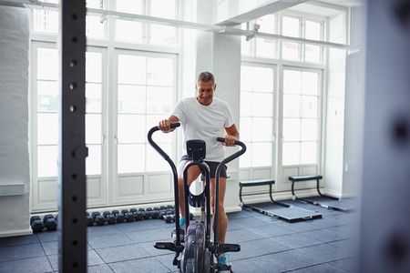 Determined mature man in sportswear pushing himself on a stationary bike while working out alone at the gym