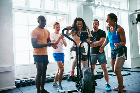 Group of people cheering on their female friend riding a stationary bike while working out together in a gym