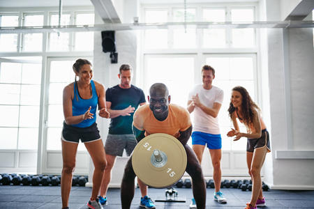 Diverse group of young people cheering on their male friend lifting weights in a gym while working out in a gym