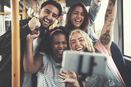 一緒にバスに乗っている間、selfie を取る様々 な若い友達グループの笑みを浮かべてください。