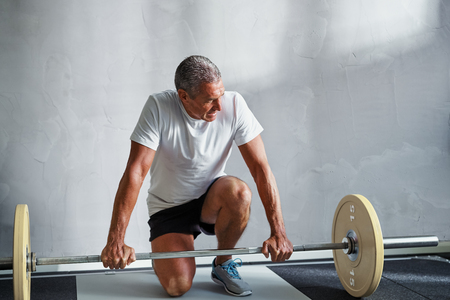 Focused mature man in sportswear kneeling in a health club preparing to lifting a barbell during a workout