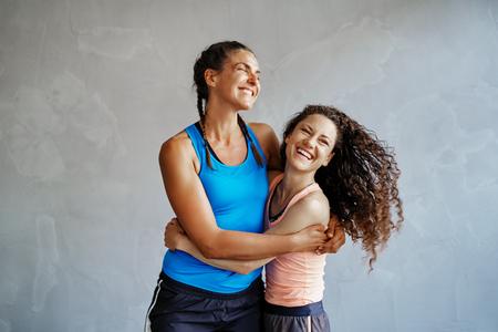 スポーツウェアを着た2人の若い女性がジムで一緒に笑い、腕を組んで立っている