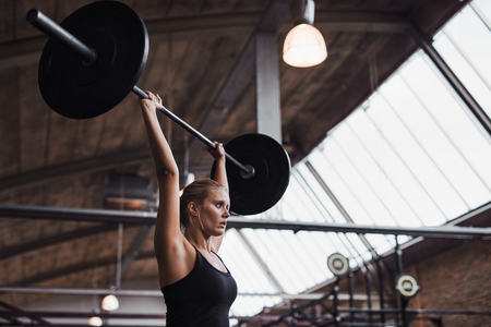 Fit young blonde woman in sportswear standing alone in a gym lifting weights over her head