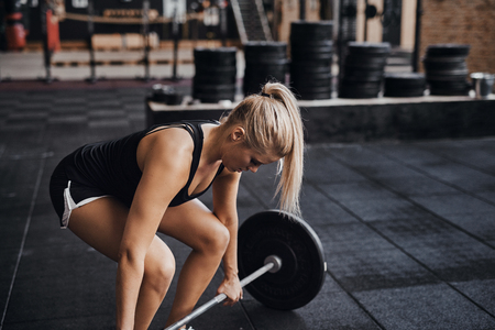 Fit young blonde woman in workout clothing preparing to lift heavy weights during strength training in a gym