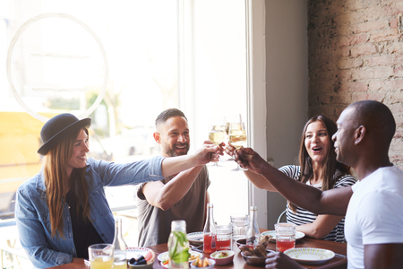 Group of diverse male and female young adults celebrating something together with wine glasses at table in restaurant