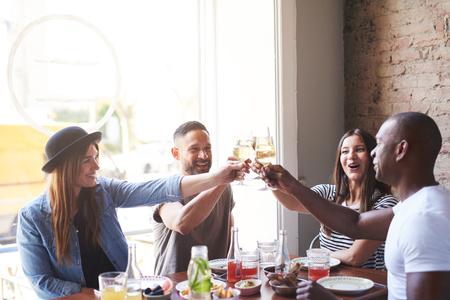 Gruppe verschiedene männliche und weibliche junge Erwachsene, die bei Tisch etwas zusammen mit Weingläsern im Restaurant feiern