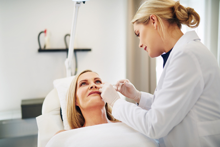 Young female doctor focused on performing a botox injection to the cheek of a mature woman lying on a table in a beauty clinic