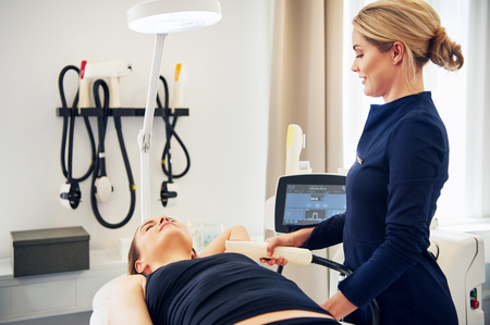Female beautician performing a laser hair removal procedure on the underarm of a young woman lying on a table in a beauty clinic