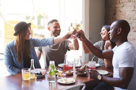 Group of four young people laughing and sitting at table in restaurant and clinking glasses with wine. Фото со стока