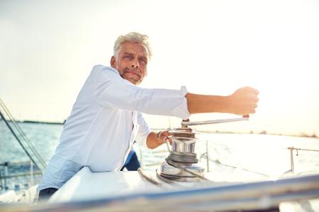 晴れた日に出航しながらウィンチを巻くボートのデッキに立つ成熟した男