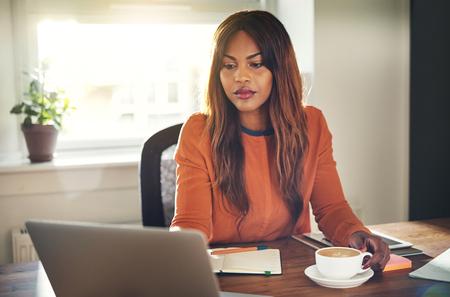 Jonge Afrikaanse vrouwelijke ondernemerszitting bij een bureau in haar huiskantoor dat een kop van koffie drinkt en online met laptop werkt