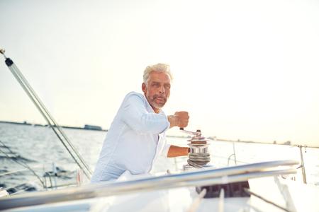 晴れた日の午後に帆のうちながらウインチを巻き船の甲板に単独で立つ中年の男性