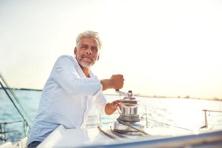 晴れた午後の帆に出かけている間、ロープウィンチを使用してボートのデッキに立っている成熟した男