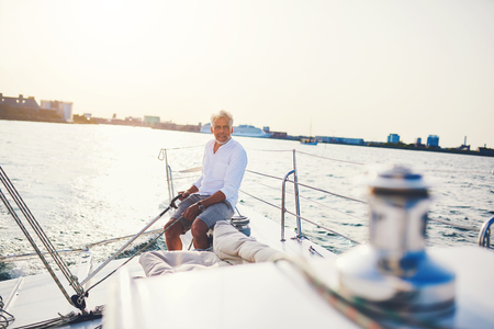 Mature man sitting on the deck of a boat steering the rudder while out for a sail along the coast on a sunny day