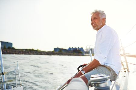 Het glimlachen rijpe mensenzitting op het dek van een boot terwijl het varen langs de kust op een zonnige dag