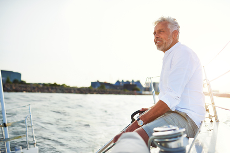 Smiling mature man sitting on the deck of a boat while sailing along the coast on a sunny day
