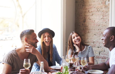 Diverse small group of four attractive laughing friends having wine and a meal together in restaurant with brick wall and bright large window in background Stock Photo