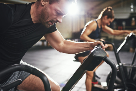 Man and woman behind riding cycling machine in hard efforts grimacing in light spacious gym. Stock Photo - 88635179
