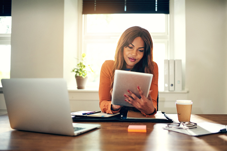 Souriante jeune africaine entrepreneur femme travaillant avec une tablette numérique tout en étant assis à une table dans son bureau de la maison Banque d'images - 88635180