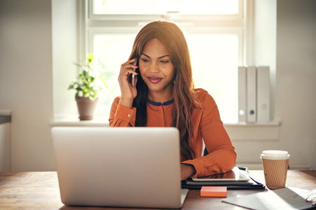 彼女の自宅のオフィスでテーブルに座っている若いアフリカの女性起業家の笑顔携帯電話で話し、ノートパソコンで作業する