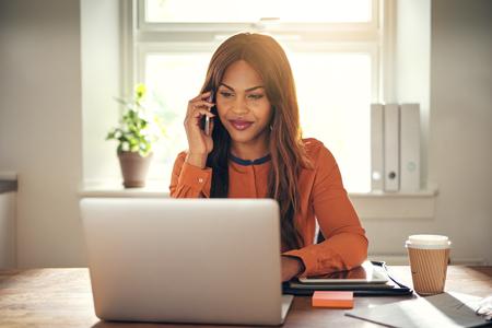 Lächelnder junger afrikanischer weiblicher Unternehmer, der an einem Tisch in ihrem Innenministerium spricht auf einem Mobiltelefon sitzt und an einem Laptop arbeitet
