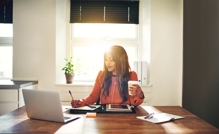 Smiling young African female entrepreneur sitting at a table in her home office writing down notes while drinking coffee and working on a laptop Stock Photo
