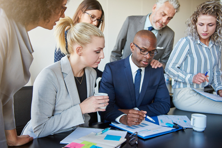 Diverse group of businesspeople discussing paperwork together while having a meeting around a boardroom table in a modern office Stock Photo
