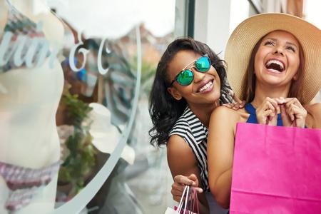 下着のウィンドウ ショッピングしながら紙のショッピング バッグを持って美しい女友達を笑い