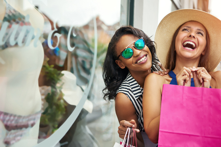 Giggling beautiful female friends holding paper shopping bags while window shopping for underwear