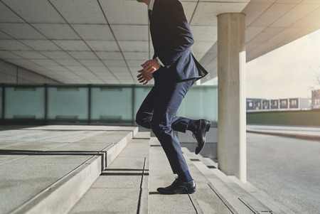 Runner businessman hurrying to office. Horizontal outdoors shot Stock Photo