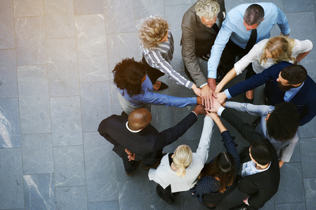 High angle view of a team of united coworkers standing with their hands together in a huddle in the lobby of a modern office building Banco de Imagens