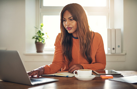 Focused young African female entrepreneur sitting at a desk in her home office drinking a cup of coffee and working online with a laptop 스톡 콘텐츠