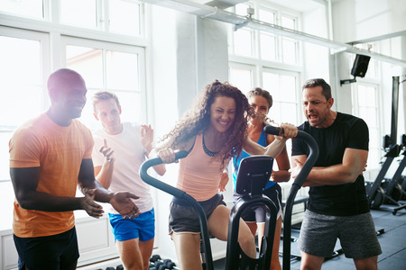 Cheering group of friends encouraging a women riding a stationary bike while working out together at the gym