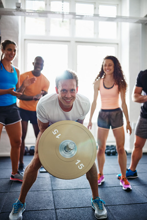 Smiling young man straining to lift weights in a gym with a diverse group of friends cheering him on in the background