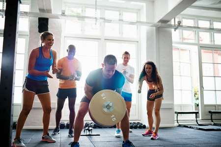 Young man straining to lift a barbell in a gym with a diverse group of friends cheering him on in the background