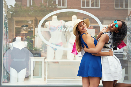 Pair of cute friends in short skirts embracing in front of window with manikins dressed in bikini swimwear or underwear Stock Photo