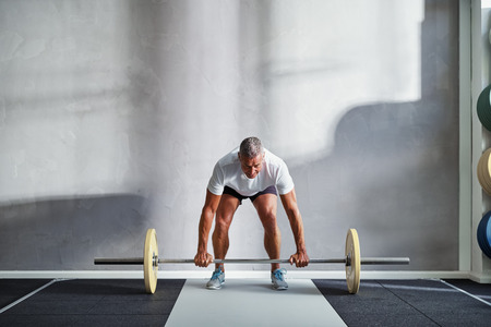 Focused mature man in sportswear standing alone in a gym lifting weights during a workout