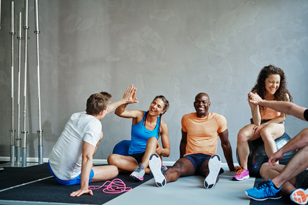 Friends in sportswear high fiving and laughing together while sitting on the floor of a gym after a workout Stock Photo