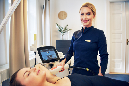 Smiling young beautician performing a laser hair removal procedure on the underarm of a young woman lying on a table in a beauty clinic
