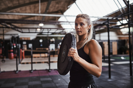 Young blonde woman in gym clohting carrying weights for a workout session while standing alone in a gym  Фото со стока