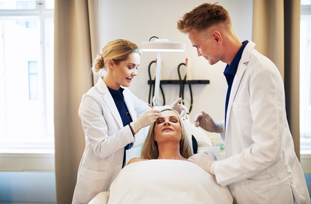 Two young doctors discussing a cosmetic surgery treatment on the face of a mature woman lying on a table in a clinic Stock Photo