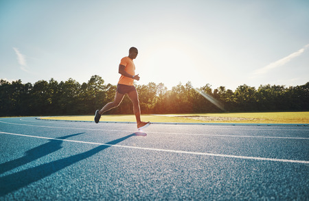 Fit and focused young African male athlete in sportswear running alone along a race track on a sunny day Stock Photo